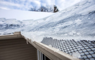 Ice dam in gutter and ice frozen on roof in winter